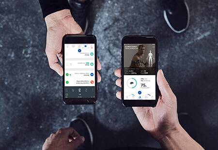 a male and female in the gym holding iphone's showing the Myprotein Fitness App wearing Myprotein Seamless Clothing